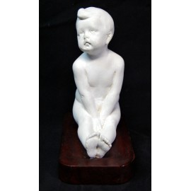 Figure of a naked boy sitting.