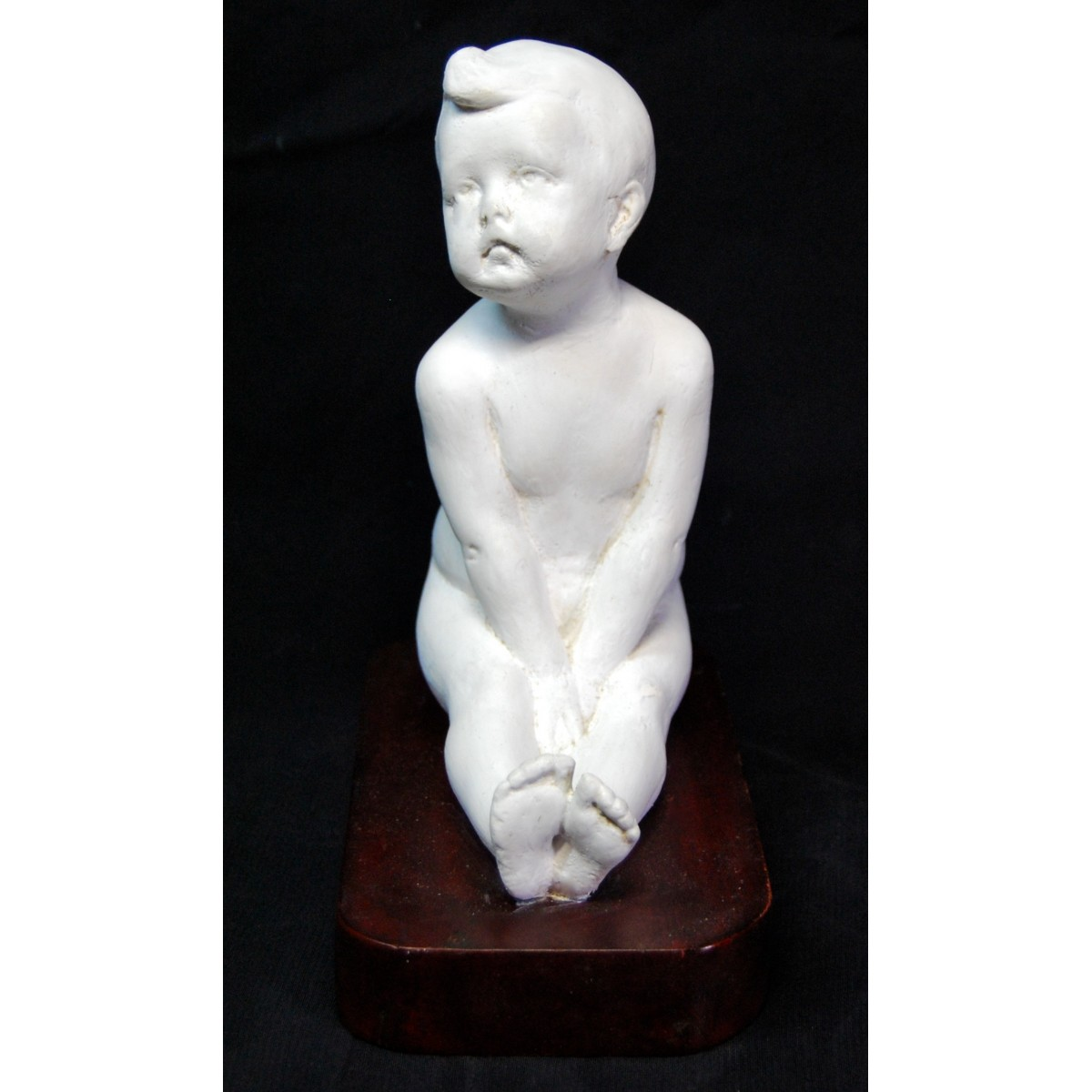 Figura de niño desnudo sentado.